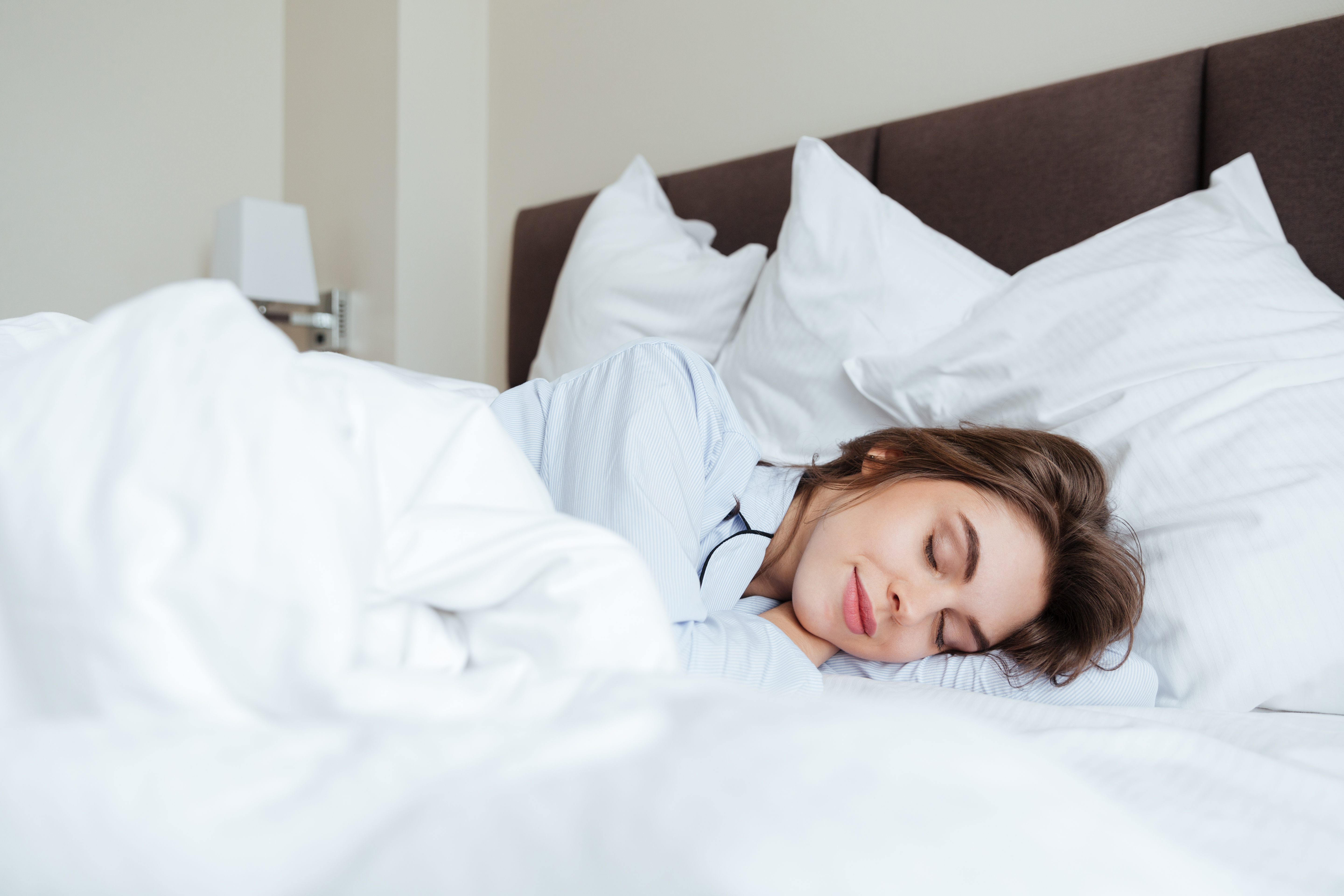 cheerful-young-lady-dressed-pajama-sleeping-bed