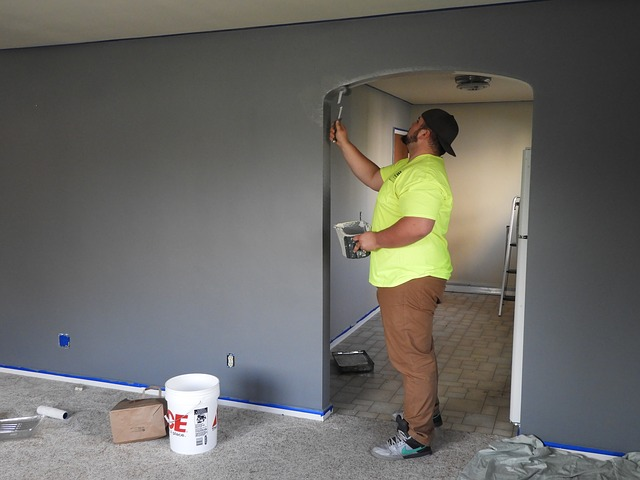 Muž, ktorý natiera stavebný otvor na dvere.jpg