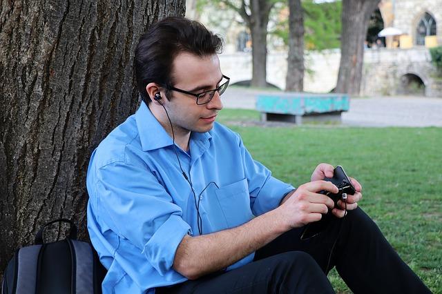 Muž sedí pri strome a počúva hudbu.jpg