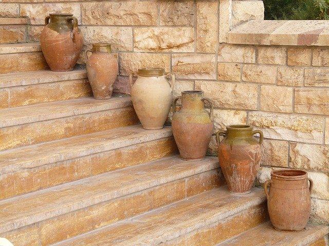 Hnedé schody z kameňa a množstvo keramiky na nich.jpg