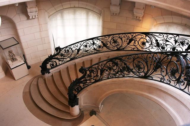 Veľké schodisko s výrazným čiernym kovaným zábradlím.jpg