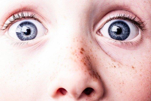 Ľudská tvár s modrými očami a pehami.jpg