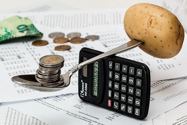 Lyžica na kalkulačke, na ktorej je zemiak a peniaze.jpg
