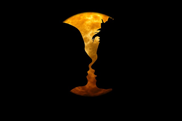 Siluety ženskej a mužskej tváre pri oranžovom mesiaci