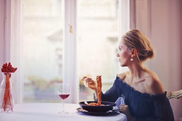 Žena sedí pri stole a obeduje